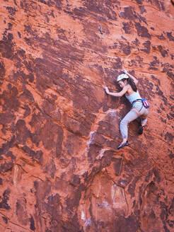 Mixed race girl rock climbing on cliff - BLEF09961