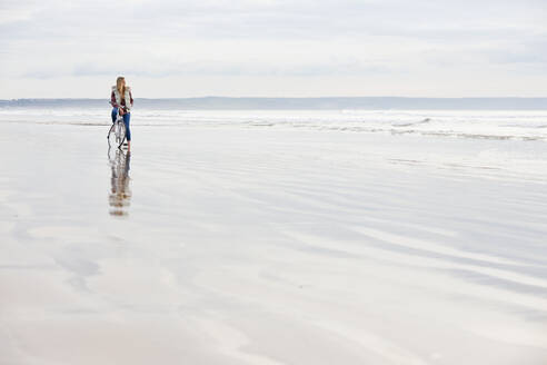 Woman with bicycle looking at ocean view on beach - JUIF02400