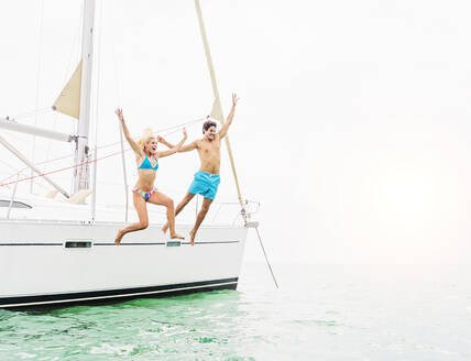 Couple jumping from sailboat - BLEF10038