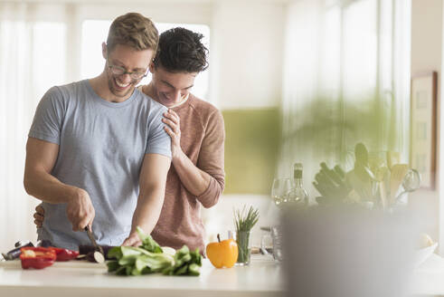 Caucasian gay couple cooking in kitchen - BLEF10077