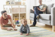 Caucasian gay fathers and baby relaxing in living room - BLEF10086