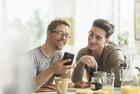 Caucasian gay couple using cell phone at breakfast - BLEF10095