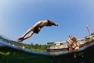 Boy diving into sunny lake - FSIF04154