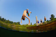 Boy somersaulting off dock into sunny summer lake - FSIF04160