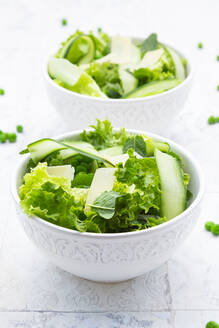High angle view of fresh salad in bowls on tiled floor - LVF08187