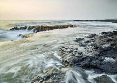 Waves splashing on volcanic rocks in Kealakekua Bay against sky during sunset - CVF01285
