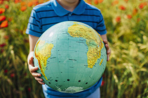 Midsection of boy holding globe in poppy field - MJ02387