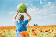 Rear view of boy holding globe in poppy field on sunny day - MJ02390