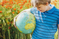 Boy holding globe in poppy field on sunny day - MJ02393