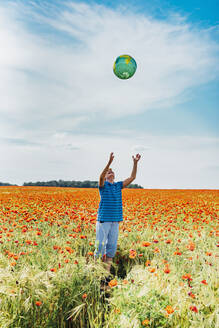 Boy catching globe while standing in poppy field against sky - MJF02396
