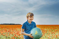Happy boy holding globe in poppy field against sky on sunny day - MJ02402
