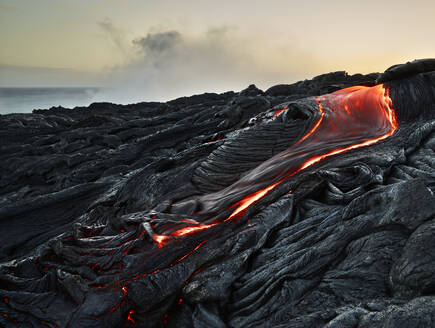 Lava flowing from Pu'u O'o' at Hawaii Volcanoes National Park against sky - CVF01294