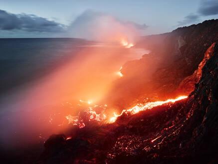 Glowing orange lava flowing from Pu'u O'o' in sea at Hawaii Volcanoes National Park against sky - CVF01297