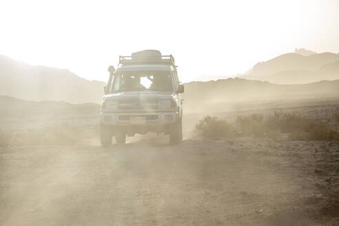 Off-road vehicle on dirt road amidst dust in desert against sky during sunset - NGF00510