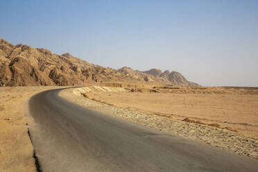 Empty road by rock formation in desert against clear blue sky - NGF00513
