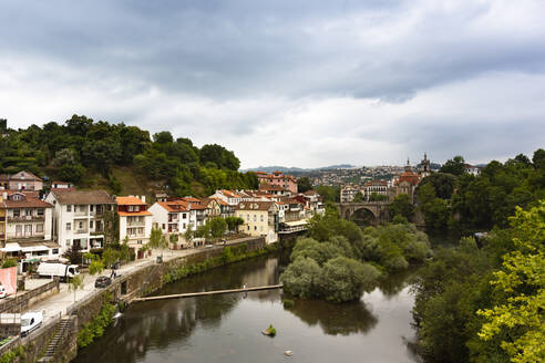 River canal by buildings in town at Duoro Valley against cloudy sky - FCF01747