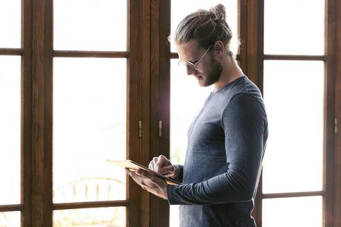 Young man at home using a digital tablet - JSRF00437