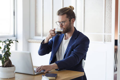 Businessman with laptop and cup of coffee at table - JSRF00458