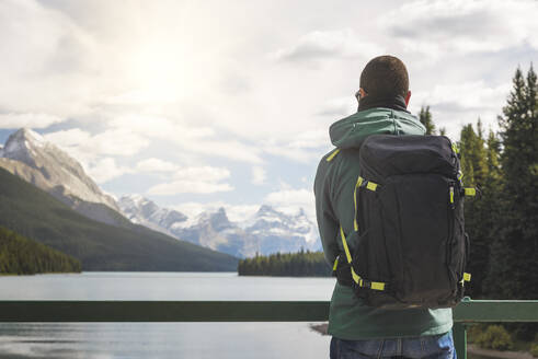 Tourist with backpack enjoying the view over Maligne Lake, Canada - EPF00596