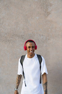 Portrait of laughing young man with backpack listening music with red haedphones - MGIF00553