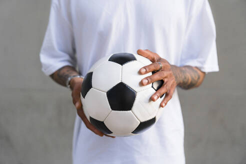 Young man's hands holding football, close-up - MGIF00562