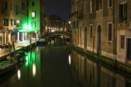 Bridge over canal amidst buildings in Venice at night - LJF00460