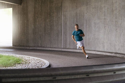 Sporty man sprinting on a street - DIGF07489