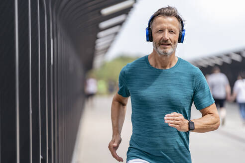 Sporty man wearing headphones and jogging - DIGF07492