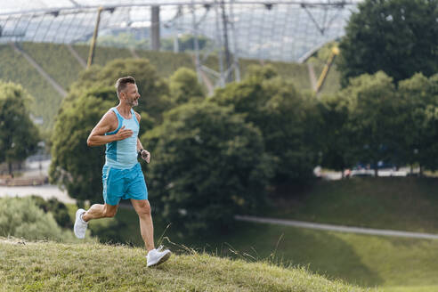 Sporty man jogging in a park - DIGF07504