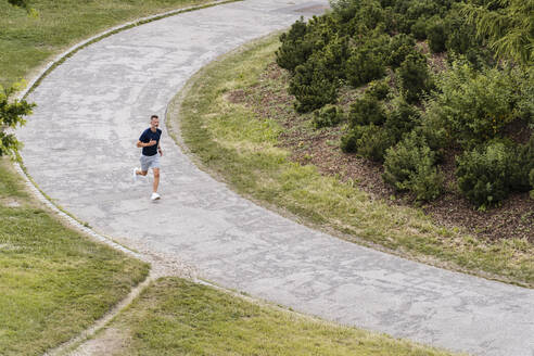 Sporty man jogging in a park - DIGF07507