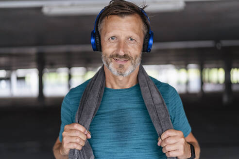 Portrait of a sporty man wearing headphones after workout - DIGF07528