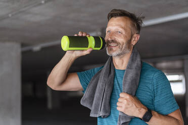 Sporty man with drinking bottle after workout - DIGF07531