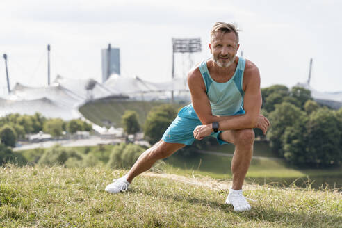 Sporty man stretching in a park - DIGF07546