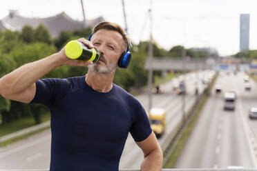 Sporty man with drinking bottle and headphones on a bridge - DIGF07555