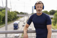 Sporty man standing on a bridge wearing headphones - DIGF07558