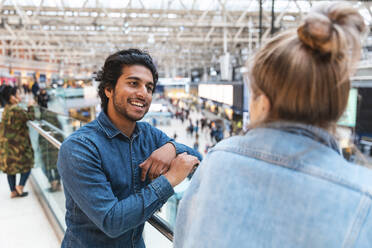 Portrait of young man talking to his girlfriend at train station - WPEF01591