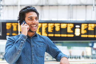 Portrait of young man on the phone at train station, London, UK - WPEF01594
