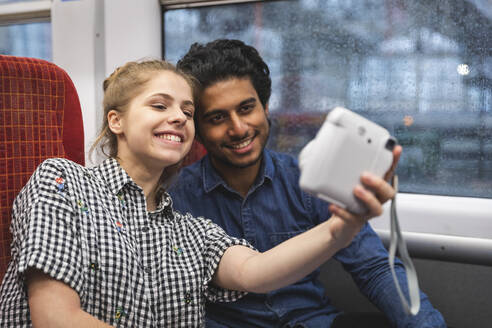 Portrait of happy young couple taking selfie with instant camera in train, London, UK - WPEF01597