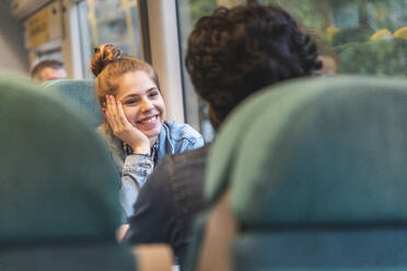 Portrait of happy young woman travelling by train with her boyfriend, London, UK - WPEF01606