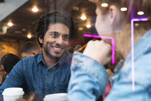 Portrait of smiling young man in a coffee shop looking at young woman - WPEF01612