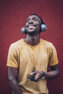Portrait of happy young man listening musiv with headphones and smartphone - OCMF00481