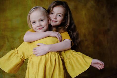 Portrait of smiling girl hugging her little sister - OGF00068