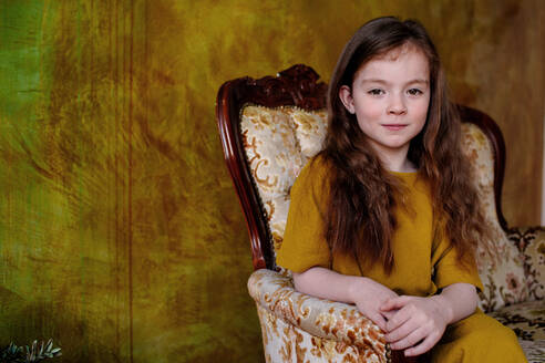 Portrait of little girl sitting on lounge chair - OGF00071