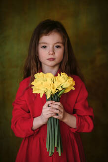 Portrait of little girl in red dress with bunch of daffodils - OGF00074