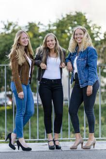 3 Frauen, 22, 23 und 24 Jahre, Lifestyle. stehen am Geländer - STSF02127