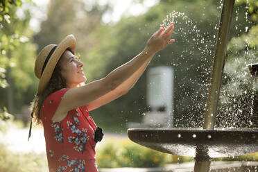 Smiling woman splashing with water of fountain in summer - FLLF00239