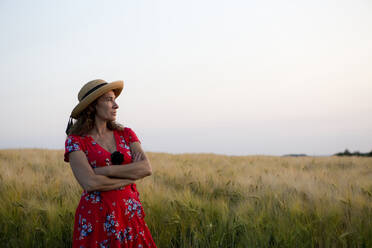 Woman wearing straw hat and red summer dress with floral design standing in front of grain field - FLLF00242
