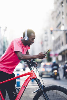 Young man with e bike and headphones using smartphone in the city - OCMF00498