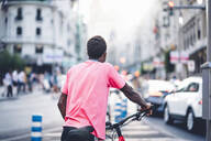 Rear view of young man with e bike in the city - OCMF00507