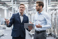 Two businessmen with tablet talking in a modern factory - DIGF07561